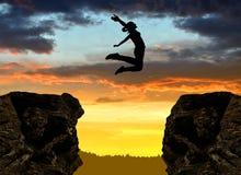 Silhouetteer het meisje die over het hiaat springen Stock Foto's