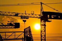 Silhouettekranbyggnad och solnedgång Arkivbild