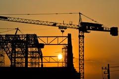 Silhouettekranbyggnad och solnedgång Royaltyfri Foto