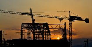 Silhouettekranbyggnad och solnedgång Royaltyfri Bild