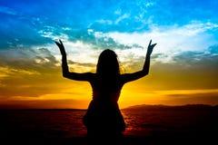 Silhouetten av kvinnan utför som yoga Fotografering för Bildbyråer