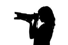 Silhouette av en flicka med en kamera Arkivfoto