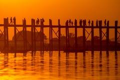 Silhouetten av U-bein överbryggar på solnedgången Arkivbild