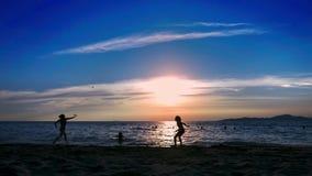 Silhouetten de mensen spelen badminton op het strand bij zonsondergang stock video
