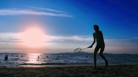 Silhouetten de mensen spelen badminton op het strand bij zonsondergang stock videobeelden