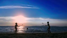 Silhouetten de mensen spelen badminton op het strand bij zonsondergang stock footage