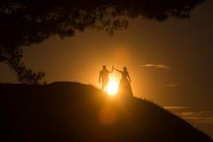 Silhouetten die van huwelijkspaar zich op heuvel bevinden Royalty-vrije Stock Fotografie