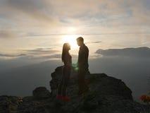 Silhouetten die van jong paar zich op een berg bevinden en aan elkaar op mooie zonsondergangachtergrond kijken Liefde van kerel Royalty-vrije Stock Foto's