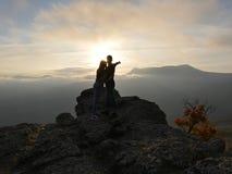 Silhouetten die van jong paar zich op een berg bevinden en aan elkaar op mooie zonsondergangachtergrond kijken Liefde van kerel Stock Fotografie