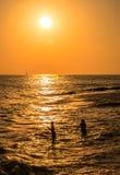 Silhouetten die van meisjes bij zonsondergang, in het overzees zwemmen Stock Afbeeldingen