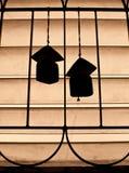 Silhouetten kopplar ihop av keramiskt lindar sätta en klocka på på fönster Royaltyfri Foto