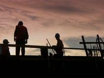 Silhouetten van arbeiders stock afbeelding