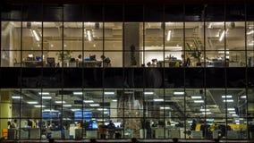 Silhouetten van creatieve beambten in het eind van werkdag stock videobeelden