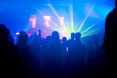Silhouetten van dansende mensen in laserlicht Royalty-vrije Stock Afbeelding