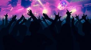 Silhouetten van dansende mensen voor heldere stadiumlichten royalty-vrije stock fotografie