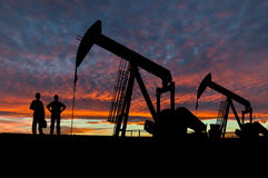 Silhouetten van de Arbeiders van Pumpjacks en van de Olie Stock Afbeelding