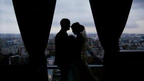 Silhouetten van de bruid en de bruidegom op de achtergrond de stad stock video