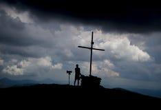 Silhouetten van de mens en een kruis op bergbovenkant royalty-vrije stock foto