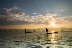 Silhouetten van de traditionele vissers die visnet du werpen Royalty-vrije Stock Foto
