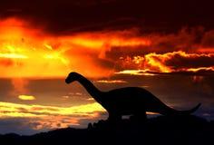 Silhouetten van dinosaurussen in het bos op zonsondergangachtergrond met exemplaarruimte royalty-vrije stock foto