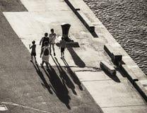 Silhouetten van een groep die mensen lange schaduwen op een asph gieten stock fotografie