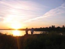 Silhouetten van een mens en een meisje op het meer in de stralen van de het plaatsen zon royalty-vrije stock fotografie