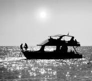 Silhouetten van een overzeese boot en mensen die op het rusten Royalty-vrije Stock Foto's