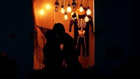 Silhouetten van een vrouw in een hoed en weinig jongen die en omhelzing op achtergrond van landschap aan Halloween communiceren stock video