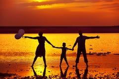 Silhouetten van familie op het meer bij zonsondergang Stock Afbeeldingen