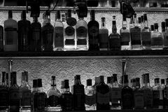 Silhouetten van flessen met alcoholtempels van schuld op een plank in een nachtclubbar Stock Fotografie