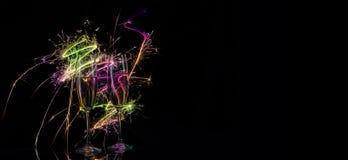 Silhouetten van glazen met champagne in multicolored vonken van Stock Afbeelding