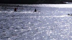 Silhouetten van groepskayakers op de rivier