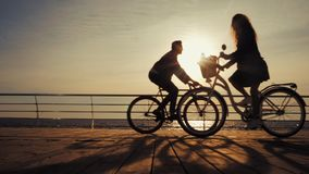 Silhouetten van jonge paar berijdende fietsen op overzeese dijk en het drijven voorbij elkaar Meisje en jongen op datum Mensen stock footage