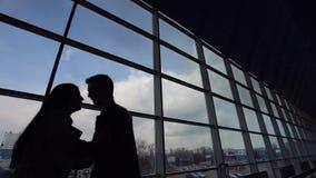 Silhouetten van jonge paarvergadering in luchthaven stock video