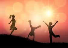 Silhouetten van kinderen die in zonsonderganglandschap spelen stock illustratie