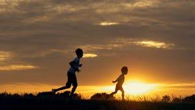 Silhouetten van lopende kinderen op een gebied bij zonsondergang stock videobeelden