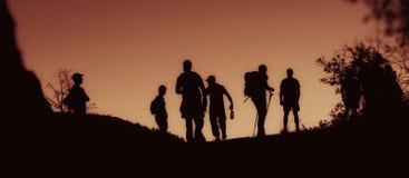 Silhouetten van lopende mensen bij schemer Royalty-vrije Stock Afbeeldingen