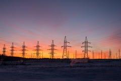 Silhouetten van machtslijnen, het thema van ecologie silhouetten op de zonsonderganghemel Machtspylonen Royalty-vrije Stock Afbeeldingen