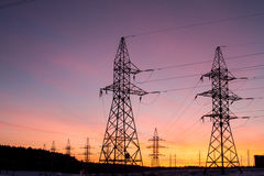 Silhouetten van machtslijnen, het thema van ecologie silhouetten op de zonsonderganghemel Machtspylonen Stock Foto's