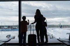 Silhouetten van mamma met jonge geitjes in terminal die op vlucht wachten royalty-vrije stock afbeeldingen