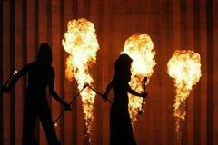 Silhouetten van mannen en vrouwen op de achtergrond van een steenmuur en brandende toortsen stock fotografie