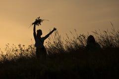 Silhouetten van meisje het plukken bloemen tijdens midzomersoltice Royalty-vrije Stock Afbeeldingen