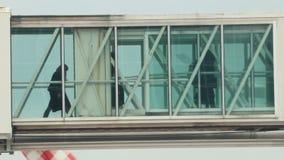 Silhouetten van mensen die aan boord door de glaspassage naar het vliegtuig gaan stock footage