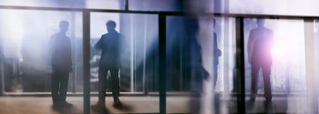 Silhouetten van mensen die in de straat dichtbij wolkenkrabbers en moderne bureaugebouwen lopen Veelvoudig blootstelling vaag bee stock fotografie