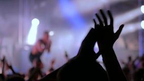 Silhouetten van mensen die en bij rotsoverleg partying slaan voor stadium stock videobeelden