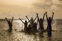 Silhouetten van mensen die in oceaan springen Stock Fotografie