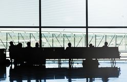 Silhouetten van mensen die op de stoelen van een luchthaven zitten die op hun vlucht wachten royalty-vrije stock fotografie