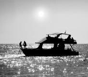 Silhouetten van mensen die op een boot zitten Stock Fotografie