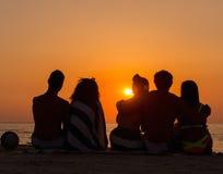 Silhouetten van mensen die op een strand zitten Stock Foto's
