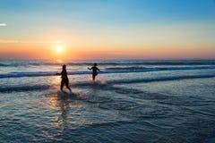 Silhouetten van mensen die van de zonsondergang op de Atlantische Oceaan genieten Royalty-vrije Stock Foto